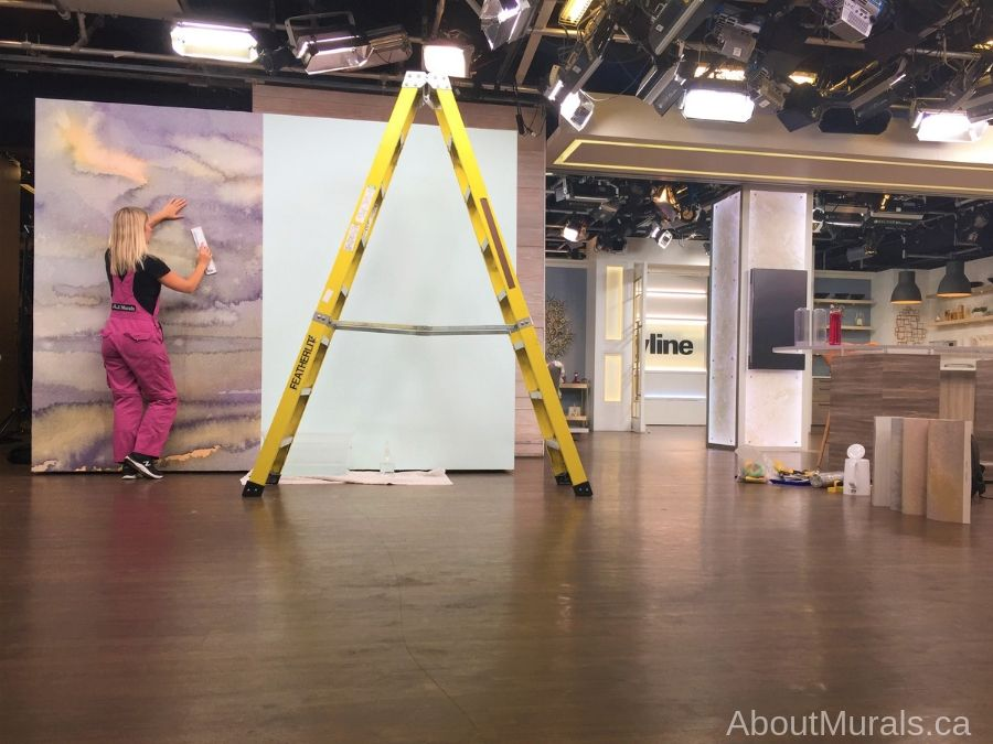 Adrienne of AboutMurals.ca hangs a meditation room wallpaper on set at Cityline