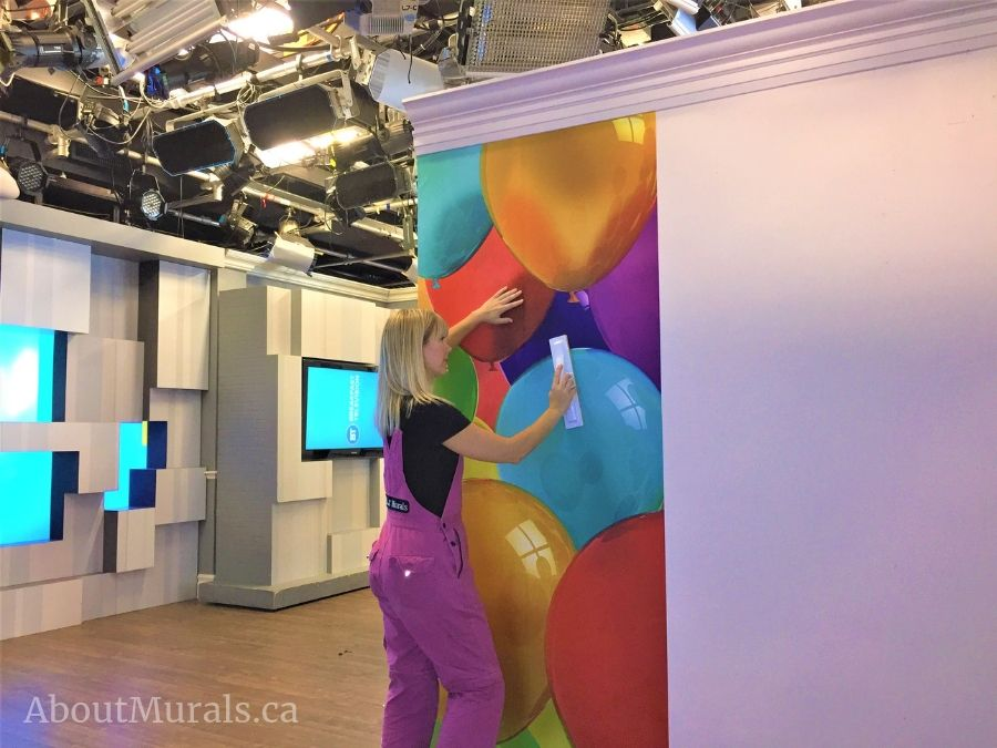 Adrienne of AboutMurals.ca hangs a party room wallpaper featuring colourful balloons on set at Cityline