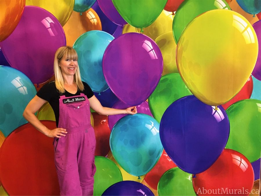 Adrienne of AboutMurals.ca stands next to a party room wallpaper full of colourful balloons