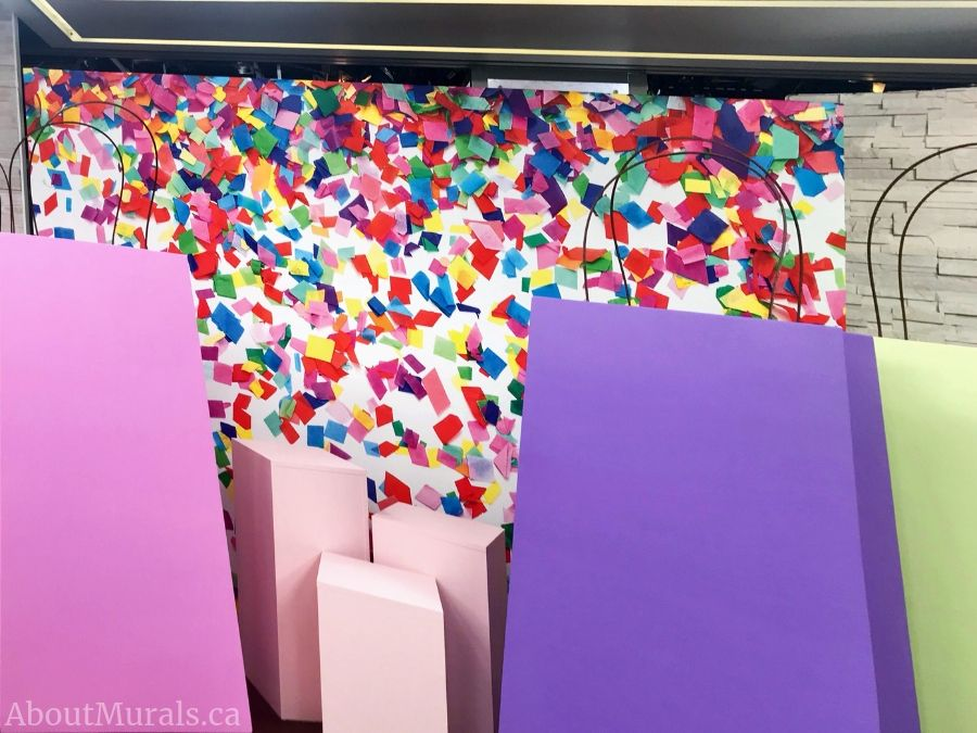 Giant swag bags sit in front of this confetti wallpaper mural sold by AboutMurals.ca