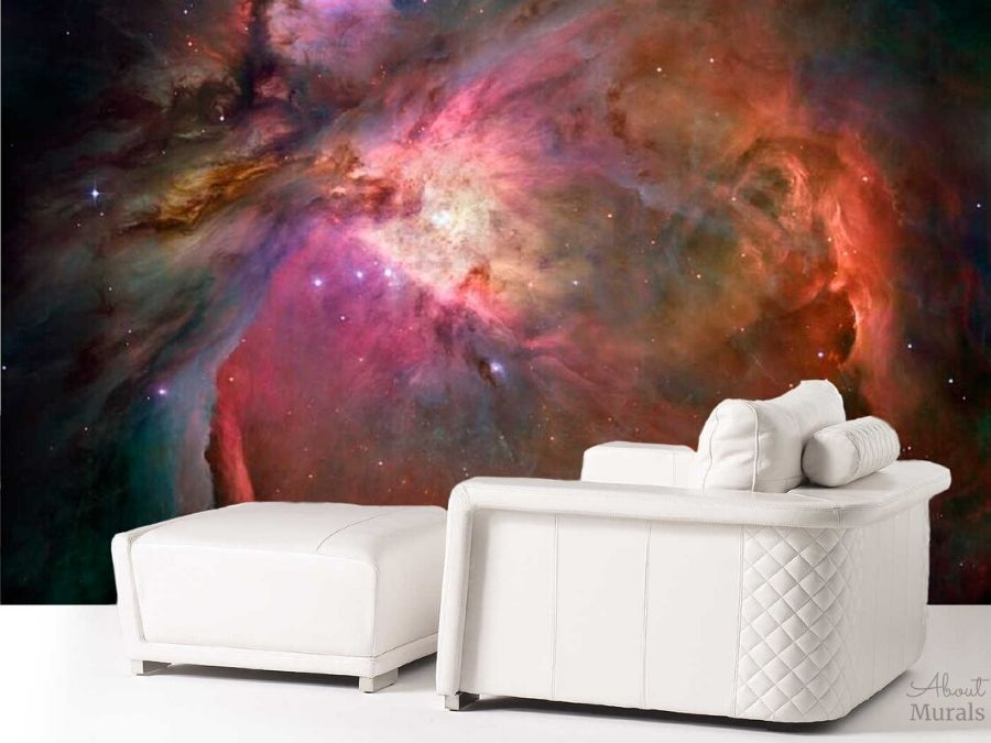 A space mural featuring the Orion Nebula is the backdrop to a living room's white chaise. AboutMurals.ca