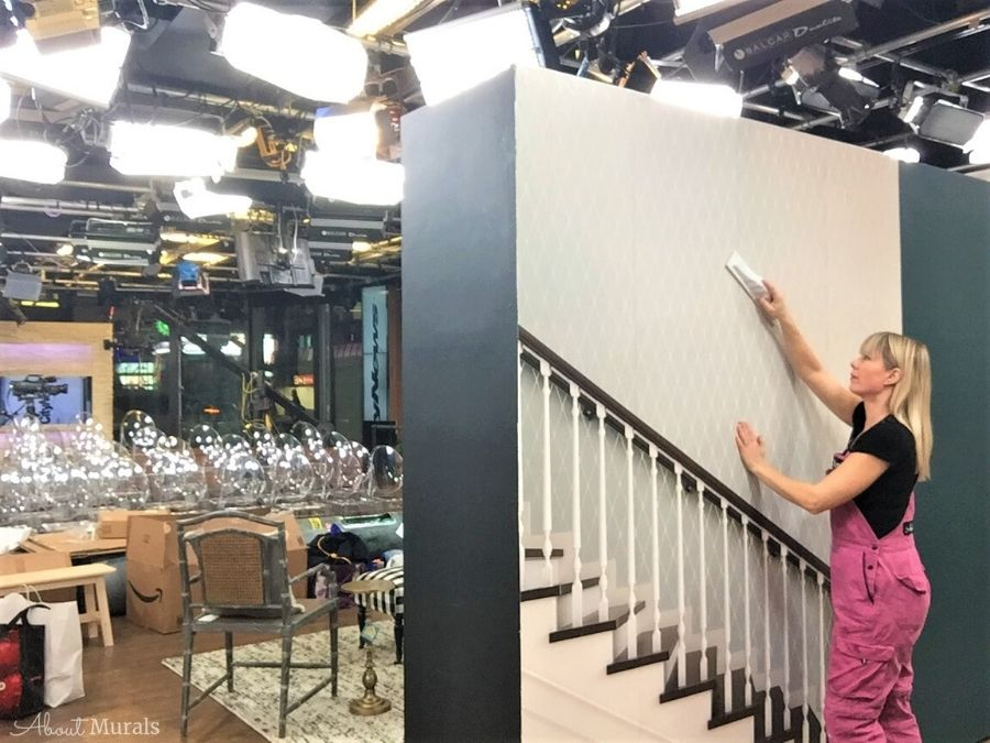 Adrienne of AboutMurals.ca installs a custom wallpaper of a staircase on set at Cityline