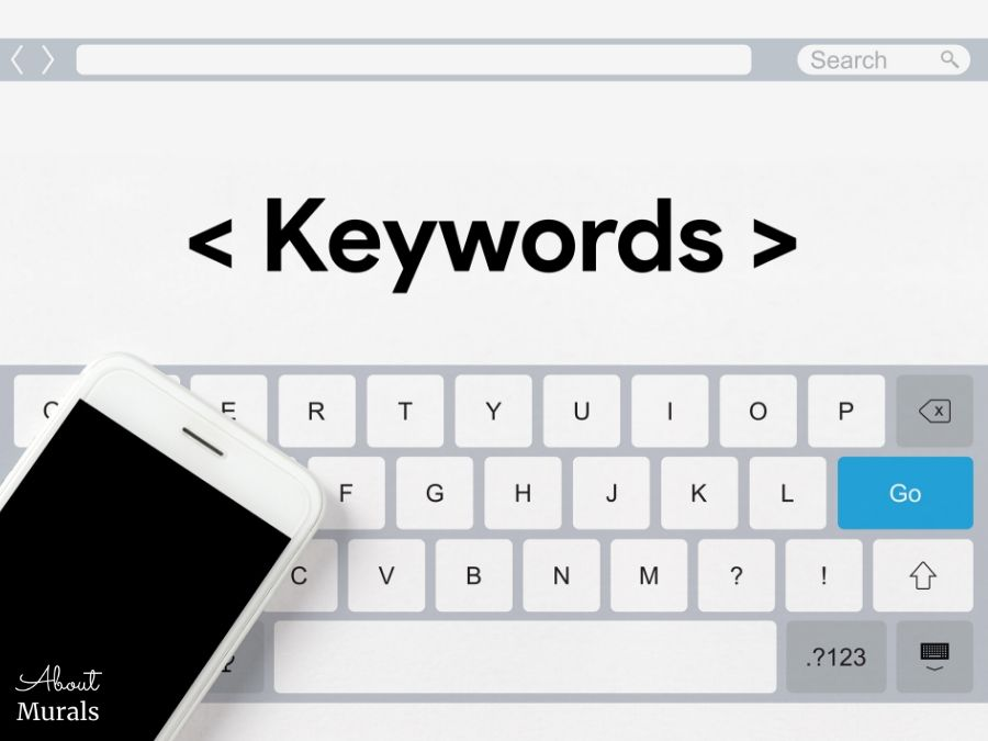 """A mobile phone is placed on top of a keyboard and the word """"Keywords"""" is above"""