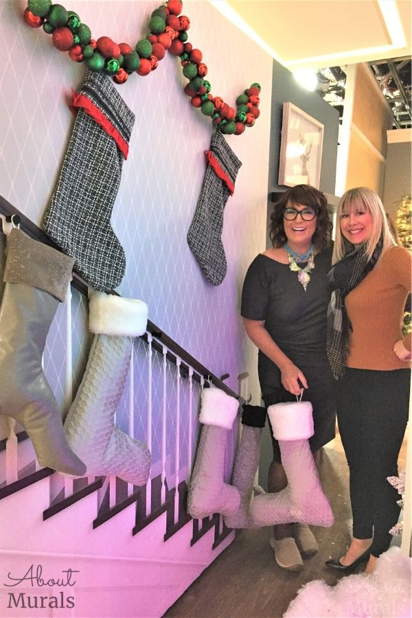 Kimberley Seldon and Adrienne Scanlan stand in front of a custom wallpaper of a staircase, decorated with Christmas stockings