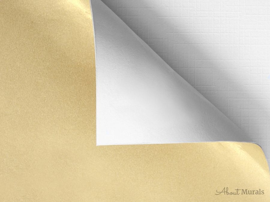 A gold piece of paper is peeled from its backing
