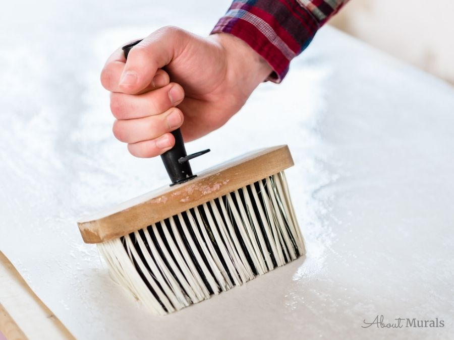 A man's hand uses a wallpaper brush to apply wallpaper paste to the back of wallpaepr