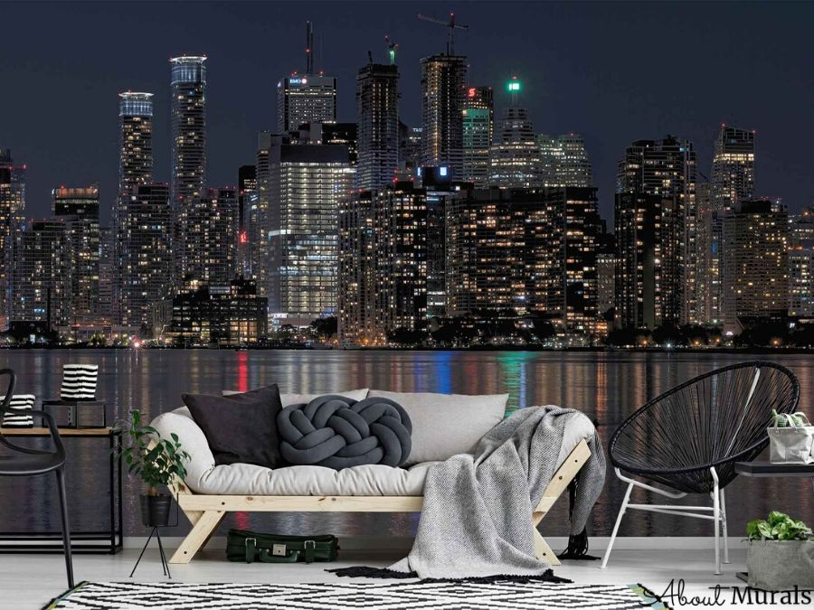 A wallpaper of Toronto's skyscrapers towering over Lake Ontario at night is the backdrop to a grey sofa in a living room. Removable wallpaper from AboutMruals.ca
