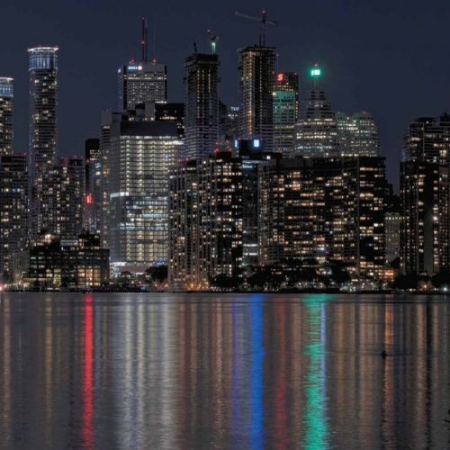 The Toronto skyline at night with lit up skyscraper buildings towering over the lake, printed on removable wallpaper from AboutMurals.ca