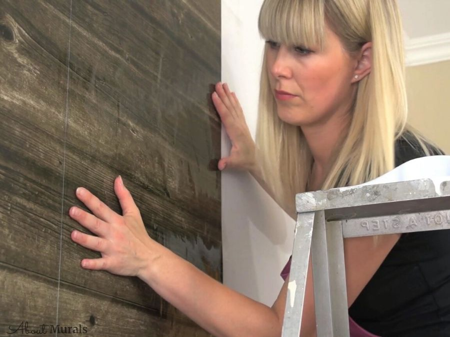 Adrienne of AboutMurals.ca slides a wallpaper panel on the wall to line up the seams