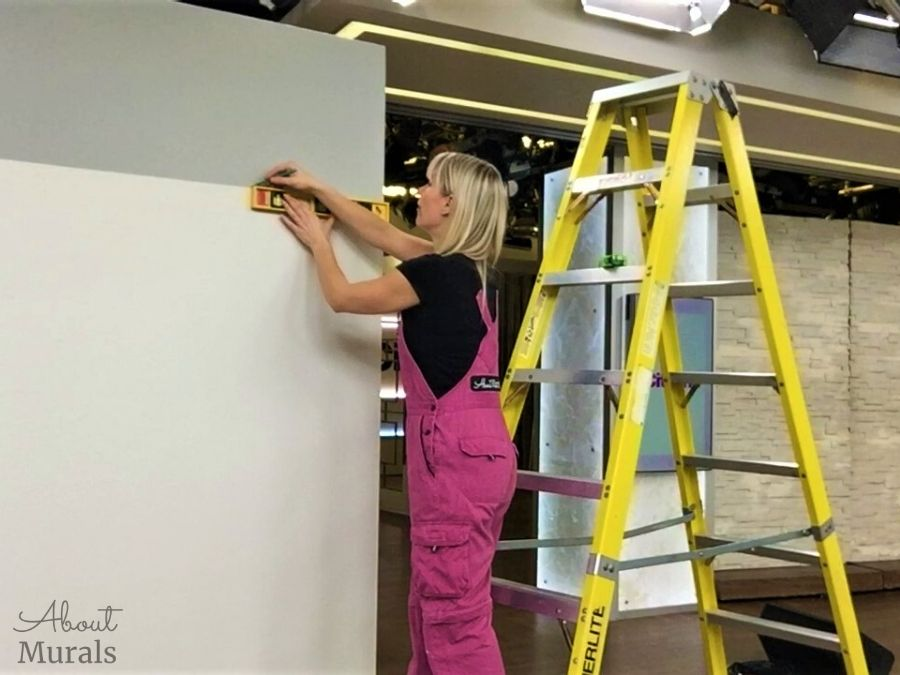 Adrienne of AboutMurals.ca draws a level, horizontal line across a wall on set at Cityline to align the top of a wallpaper mural to