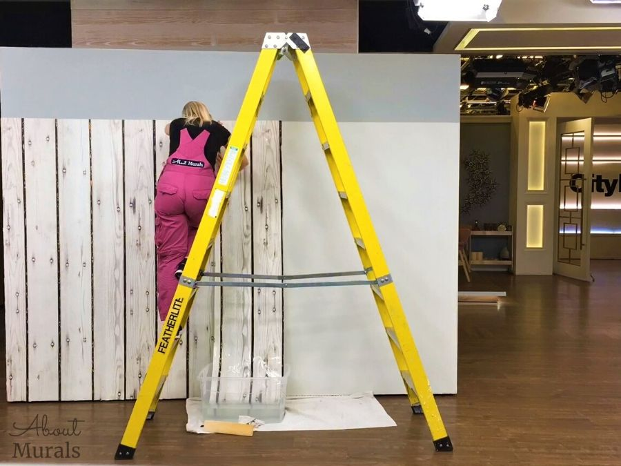 Adrienne of AboutMurals.ca hangs wallpaper against a horizontal line in order to center it on a wall
