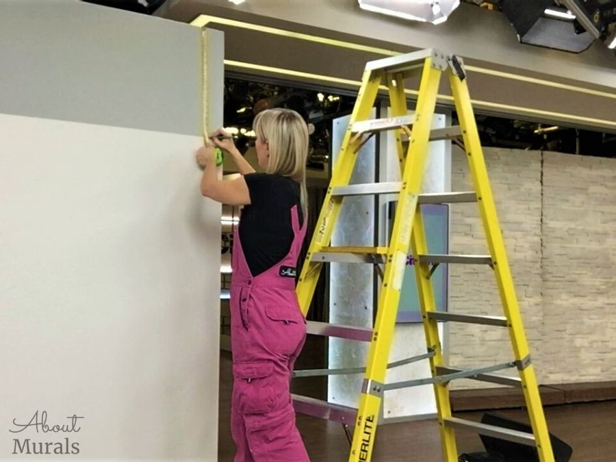 Adrienne of AboutMurals.ca measures and makes a mark where she'll be hanging a wallpaper centered horizontally on a wall on set at Cityline